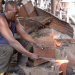 Fundi creating an iron hammer head